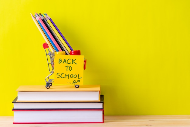 De volta ao material escolar. livros e fundo amarelo na mesa de madeira