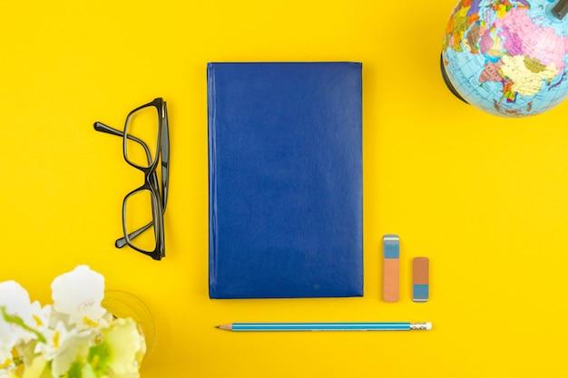 De volta ao plano de fundo do conceito de escola e composição plana leiga com diário ou caderno azul, óculos e papelaria escolar, foto de vista superior