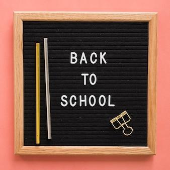 De volta ao texto da escola na lousa com lápis e clip de buldogue no cenário colorido