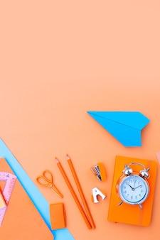 De volta às aulas, cena estilizada com material escolar em fundo azul e laranja de vista superior