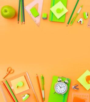 De volta às aulas com estilo de cena plana com material escolar laranja e verde em fundo laranja liso
