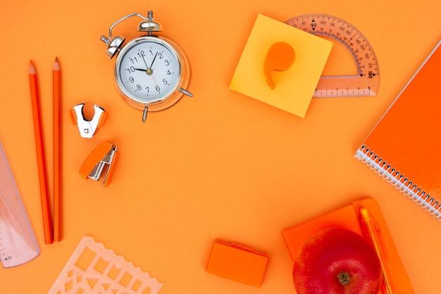 De volta às aulas com moldura plana com material escolar em fundo laranja, vista superior