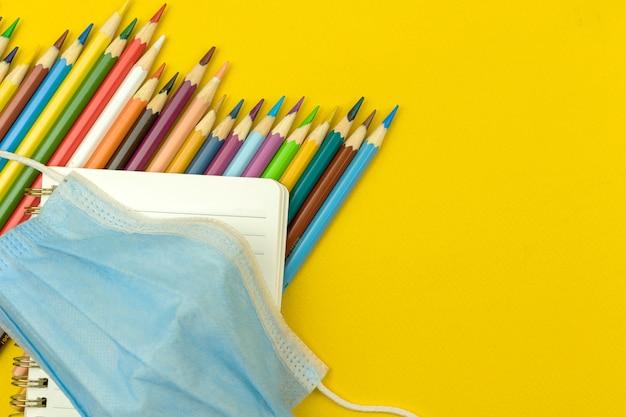 De volta às aulas, conceito de coronavírus pandêmico, composição plana, material escolar e artigos de papelaria na área de trabalho amarela, espaço de cópia e foto de vista superior