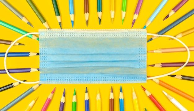 De volta às aulas durante a pandemia de coronavírus, conceito de educação com máscara médica, lápis de cor na área de trabalho amarela, foto da vista superior