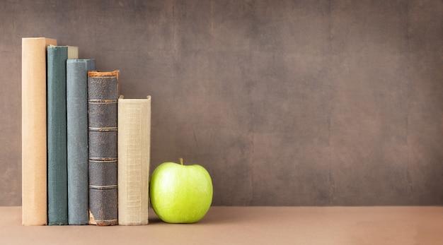 De volta às aulas e ao conceito de educação uma pilha de livros e uma maçã verde perto do quadro-negro e um lugar para o texto