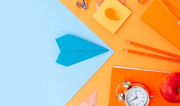 De volta às aulas em estilo borda da vista de cima com material escolar e avião de papel em fundo laranja, vista de cima