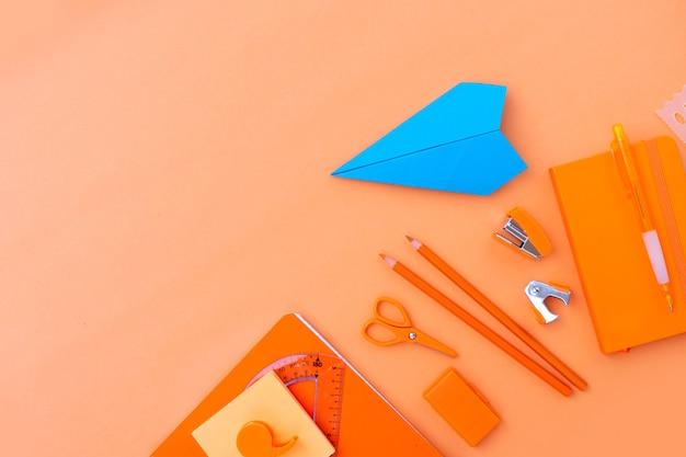 De volta às aulas em estilo fronteira com material escolar e avião de papel em fundo laranja com espaço de cópia