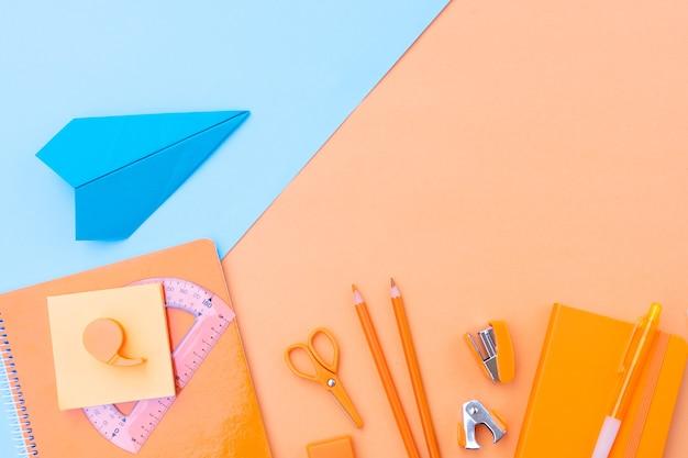De volta às aulas em estilo vista de cima, borda plana com material escolar e avião de papel em fundo laranja