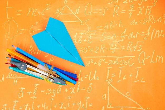 De volta às aulas, material escolar com estilo e avião de papel azul em fundo laranja escolar com espaço de cópia