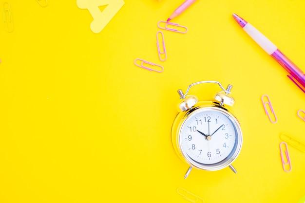 De volta às aulas ou escritório chiqueiro cena com despertador prata e espaço de cópia em fundo amarelo, plano lay
