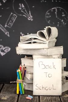 De volta às aulas, pilha de livros e material escolar no fundo do quadro-negro pintado com giz, conceito de educação