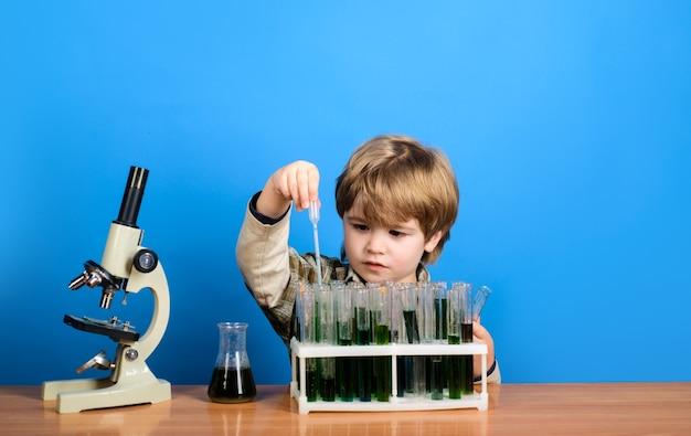 De volta às aulas química alquimia biologia experimento matéria escolar menino inteligente com tubos de ensaio