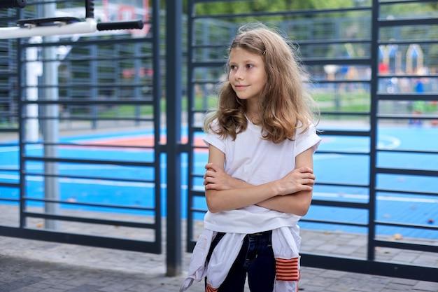 De volta às aulas, retrato de uma menina confiante de 8, 9 anos, perto da quadra de basquete da escola. o início dos estudos, esportes, avançar novos conhecimentos e habilidades