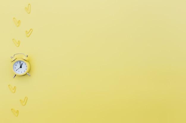 De volta às aulas, trabalho de escritório conceitual plano lay com despertador, clipes e área de espaço de cópia para texto. conceito de hora de trabalhar, estar na hora e acordar cedo ideia. fundo amarelo e despertador