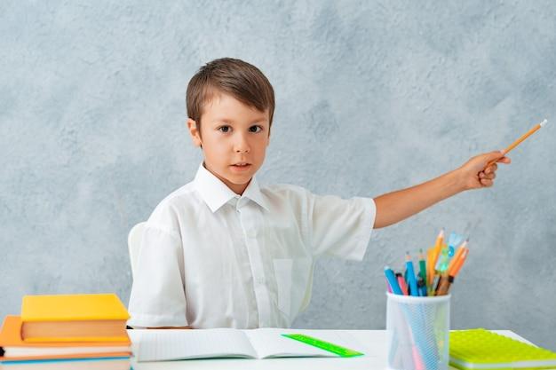 De volta às aulas, um estudante feliz e sorridente desenha na mesa um estudante resolve seu dever de casa um menino de el ...