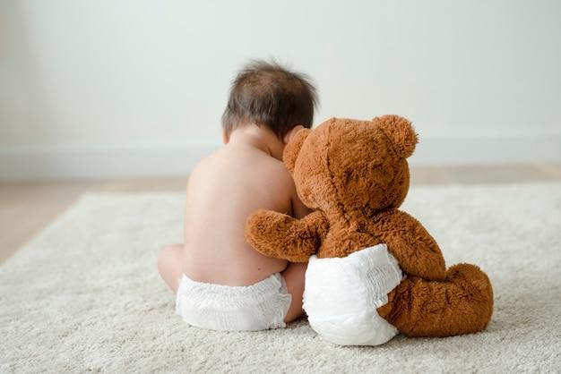 De volta de um bebê com um ursinho de pelúcia