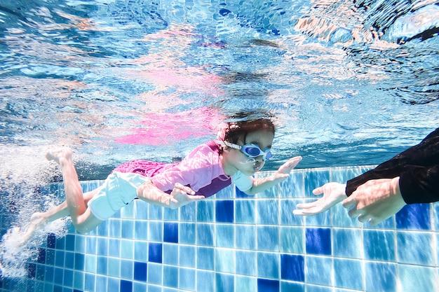 Debaixo d'água jovem menina bonitinha está nadando na piscina com seu professor de natação.