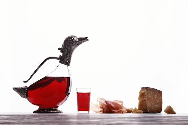 Decanter com vinho em forma de patos, copo com vinho, presunto de parma e caro queijo azul. sobre fundo branco.