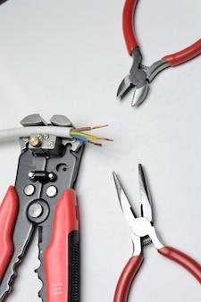 Decapador de fio, fio blindado de três núcleos e cortadores de fio em um fundo branco.