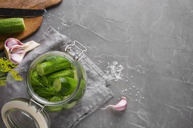 Decapagem e pepino de fermentação em frasco de vidro com endro e alho na mesa de concreta cinza escura. fechar-se. vista de cima.
