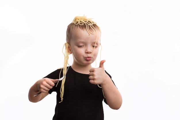 Decepção, macarrão nas orelhas. um garoto de camiseta preta não é um fundo branco e isolado. conceito de april fools day.