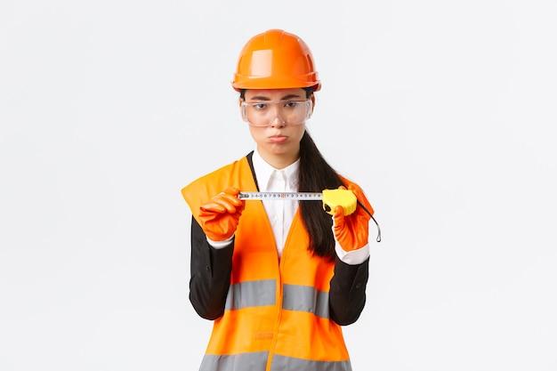 Decepcionada e sombria engenheira de construção asiática, arquiteta mostrando tamanho pequeno na fita métrica, fazendo beicinho chateado com as medições, parado descontente com o capacete de segurança, fundo branco
