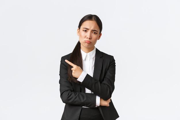 Decepcionada sombria empreendedora asiática perdendo o emprego fracassado em pé de terno fazendo beicinho e apontando o dedo esquerdo no fracasso empresária chateada compartilhando más notícias na parede branca