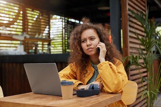 Decepcionado e triste com as más notícias, jovem morena de cabelos cacheados sentada no terraço de um café, trabalha em um laptop, falando ao telefone com um amigo. vestindo um casaco amarelo.