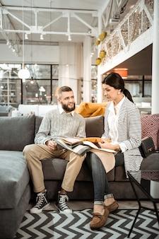 Decidir sobre o equipamento. casal concentrado inspecionando atentamente amostras coloridas e discutindo momentos de design de interiores