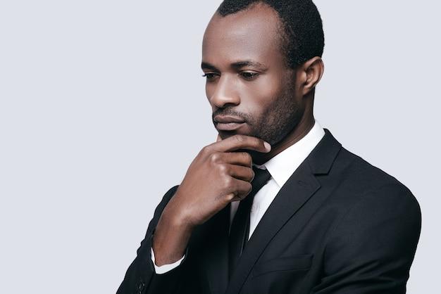 Decisão difícil. retrato de um jovem africano confiante segurando a mão no queixo e olhando para longe em um fundo cinza