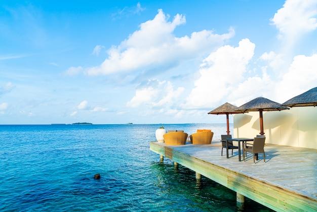 Deck de madeira ao ar livre vazio e cadeira com oceano azul nas maldivas