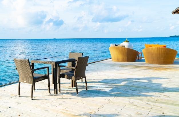 Deck do pátio ao ar livre vazio e cadeira com oceano azul nas maldivas