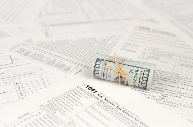 Declaração de rendimentos para o formulário estates and trusts com rolo de notas de dólar americano