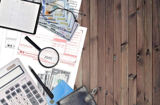 Declaração de salário e imposto w-2 do formulário do irs encontra-se na mesa plana do escritório