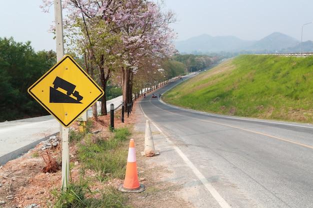 Declive sinal de trânsito para baixo na estrada bela montanha