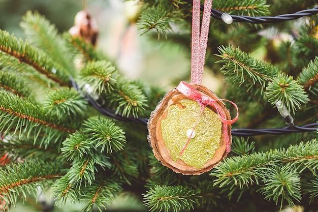 Decoração artesanal de disco de madeira na árvore de natal. idéias diy para crianças. conceito de meio ambiente, reciclagem, reciclagem e desperdício zero. foco seletivo, espaço de cópia