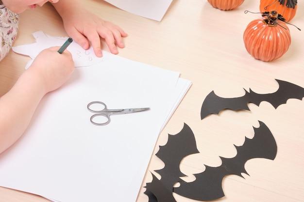 Decoração artesanal de halloween. a criança faz uma decoração de halloween com papel, a menina desenha abóboras e fantasmas em papel branco