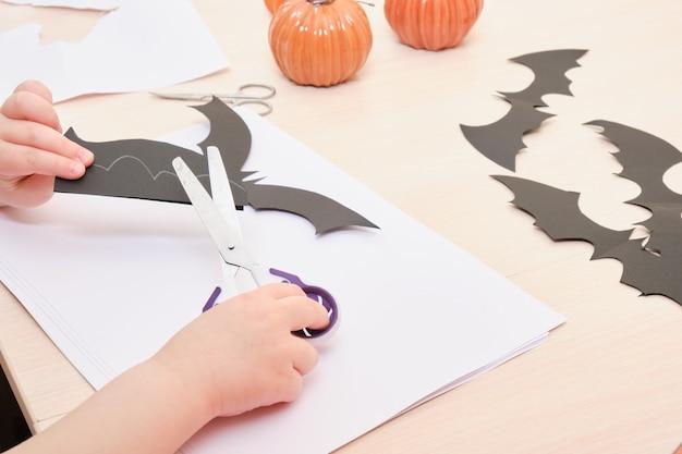 Decoração artesanal de halloween. criança corta um morcego de papel preto