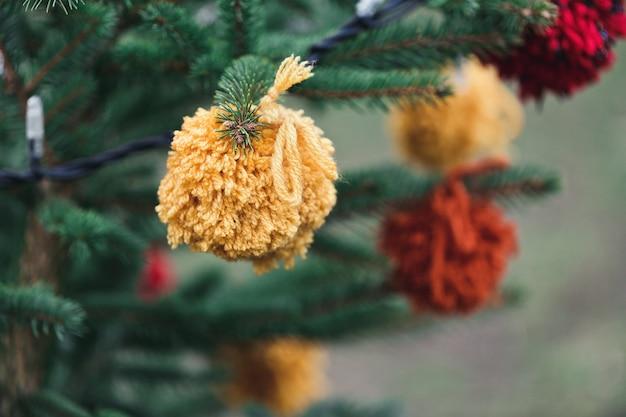 Decoração artesanal de lã em uma árvore de natal. artesanato de fios, reciclagem e conceito de desperdício zero