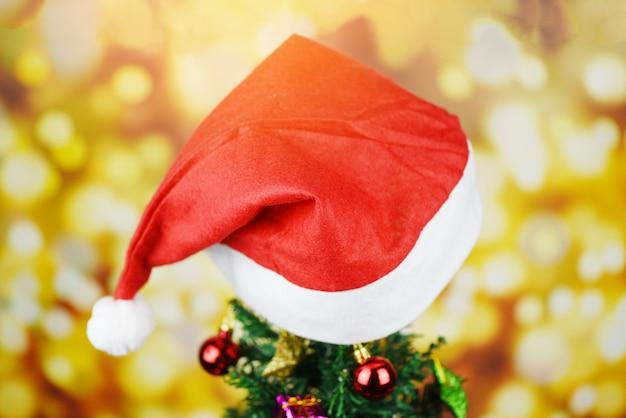 Decoração bonita chapéu de natal - árvore de natal com papai noel chapéu vermelho bola caixa de presente estrela e luzes decoradas pinheiro celebração do festival de férias de ano novo