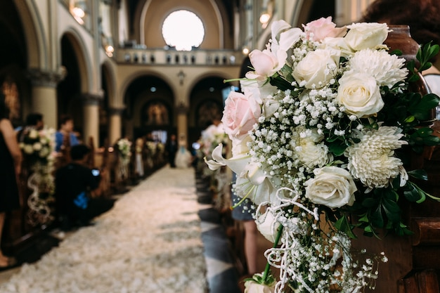 Decoração bonita do ramalhete da flor para o casamento em uma igreja com fundo do borrão.