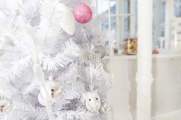 Decoração branca da árvore de natal com ouropel cor-de-rosa, de prata e branco, bolas do glitter.