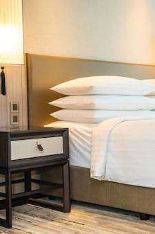 Decoração branca de travesseiro e cobertor confortável no interior da cama do quarto