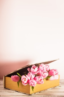 Decoração chique surrada - tulipas cor de rosa em livro vintage com espaço de cópia