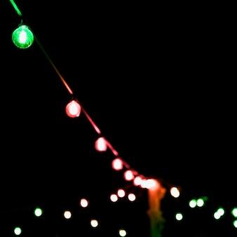 Decoração colorida da luz de natal contra o fundo preto