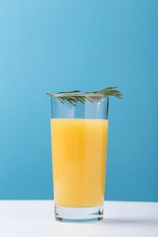 Decoração com copo de suco de laranja e ervas