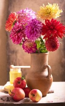 Decoração com flores dália em amarelo e laranja em vasos de terracota.