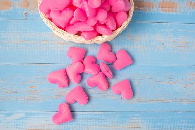 Decoração cor-de-rosa da forma do coração na cesta no fundo de madeira azul da tabela. amor, casamento, romântico e feliz dia dos namorados conceito de férias