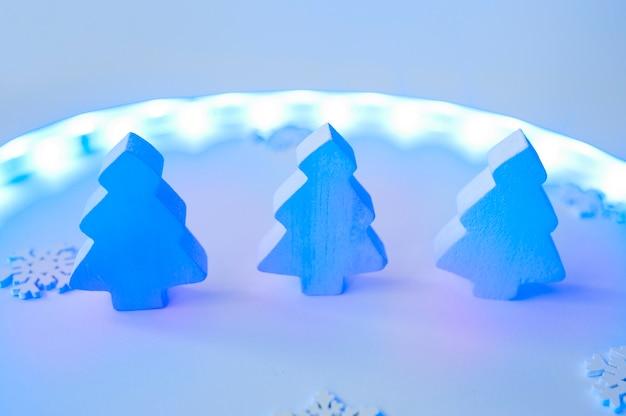 Decoração criativa de árvores de natal de madeira branca em fundo roxo neon