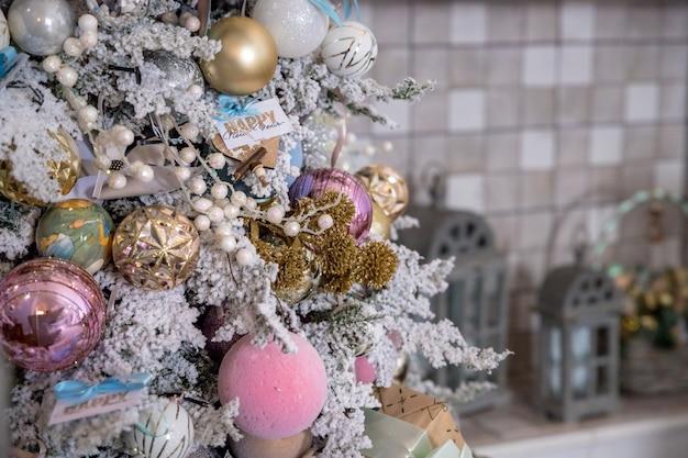 Decoração da árvore de natal. bolas de natal em ouro, prata, enfeites de natal rosa e branco, bolas de glitter e uma estrela de floco de neve. decoração para casa festiva. linda árvore de natal decorada